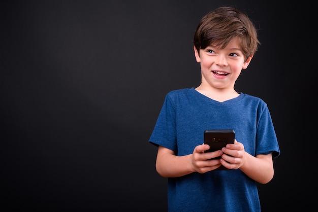 전화를 사용하는 동안 생각 행복 젊은 잘 생긴 소년의 초상화