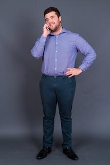 행복 한 젊은 잘 생긴 과체중 수염 된 사업가의 초상화 전화 통화