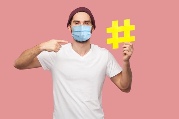 Портрет счастливого молодого хипстера с хирургической медицинской маской в белой рубашке и повседневной шляпе, держащего желтый хэштег и указывая на него пальцем. крытый, изолированный, студийный снимок, розовый фон