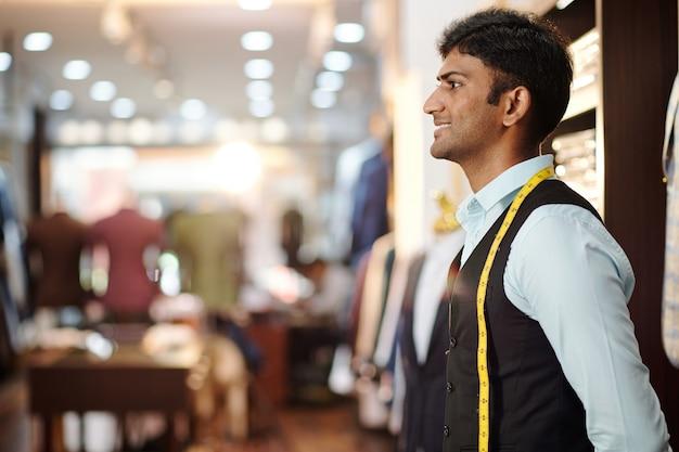 完成したオーダーメイドのスーツを見て測定テープで幸せな若いインドの仕立て屋の肖像画