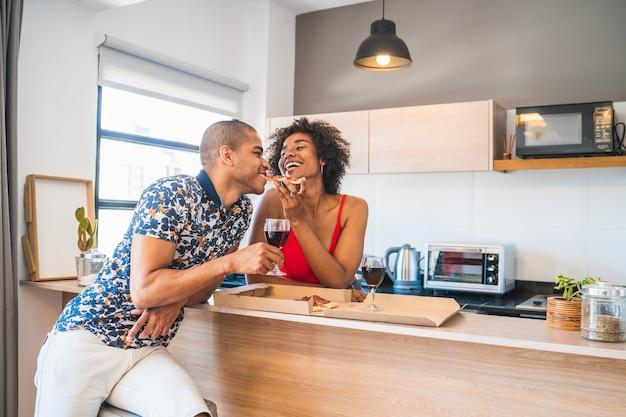 新しい家で夕食を楽しんで、幸せな若いラテンカップルの肖像画。ライフスタイルと人間関係の概念。