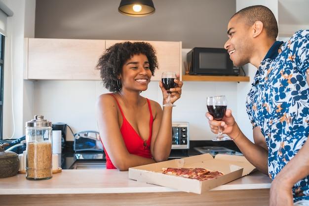 新しい家で夕食を楽しんでいる幸せな若いラテンカップルの肖像画。