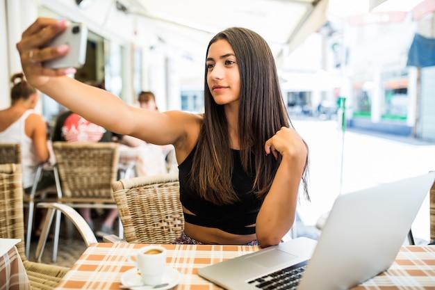 Портрет счастливой молодой латинской девушки, делающей селфи с мобильным телефоном, сидя в кафе на открытом воздухе