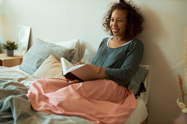 Портрет счастливой молодой латинской женщины с вьющимися каштановыми волосами, расслабляющейся дома, сидя на кровати с открытой книгой, наслаждаясь чтением