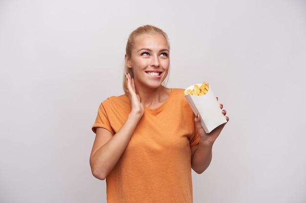 Портрет счастливой молодой прекрасной блондинки с повседневной прической, кусающей нижнюю губу и предвкушающей, как будто она ест картофель фри, весело улыбаясь на белом фоне