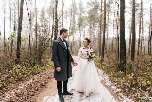 森の路地で新郎新婦の幸せな若い恋人たちの肖像画。結婚式の日