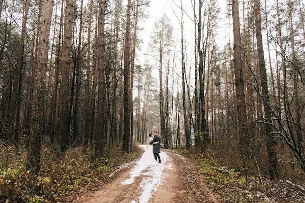 森の路地で新郎新婦の幸せな若い恋人たちの肖像画
