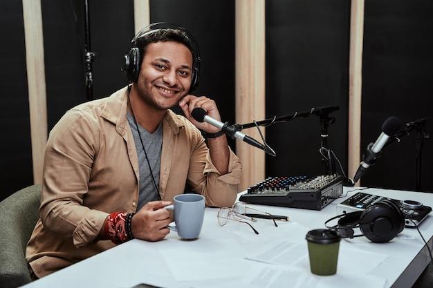 라이브를 중재하는 동안 카메라를 보며 웃고 있는 음료를 마시는 행복한 젊은 남성 라디오 진행자의 초상화