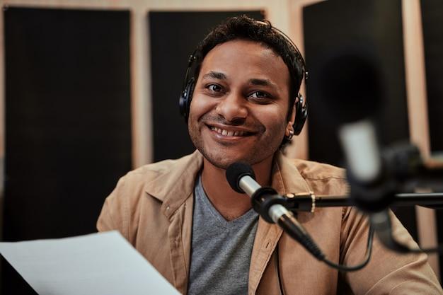 방송 중에 카메라를 보며 웃고 있는 헤드폰을 끼고 행복한 젊은 남성 라디오 진행자의 초상화