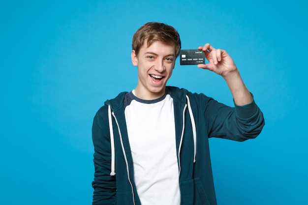青い壁に分離されたクレジット銀行カードを保持しているカジュアルな服を着て幸せな若い男の肖像画。人々の誠実な感情、ライフスタイルのコンセプト。