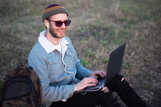 公園で幸せな若い男の肖像画、バックパックの近くの足にラップトップで座ってメガネと帽子を身に着けているジーンズのジャケットに身を包んだ