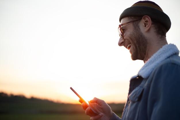 Портрет счастливого молодого человека со смартфоном в руке на фоне заката