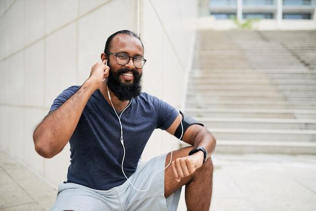 야외에서 귀에 이어폰을 꽂는 수염을 가진 행복한 젊은 혼혈 남자의 초상화