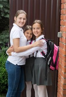Портрет счастливой молодой матери, обнимающей своих дочерей перед школой