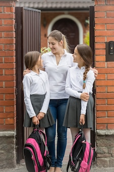 学校に向けて出発する娘たちを見ている幸せな若い母親の肖像画