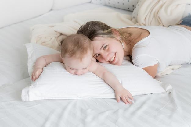 그녀의 9 개월 된 아기와 함께 큰 베개에 누워 행복 한 젊은 어머니의 초상화