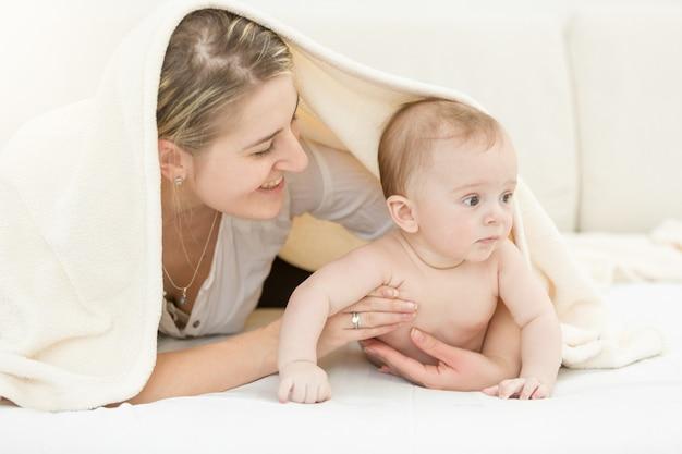 6개월 된 아들과 함께 침대에 누워 있는 행복한 젊은 어머니의 초상화