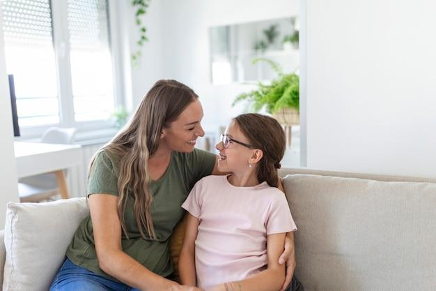 幸せな若い母親の肖像画は抱擁と抱擁を再生します愛かわいい小さな未就学児の娘がリビングルームでリラックスし、笑顔のお母さんと小さな女の子の子供の休息は一緒に家で家族の週末をお楽しみください