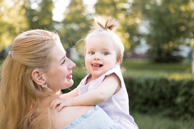 함께 시간을 보내는 작은 귀여운 아기 딸과 함께 행복 한 젊은 어머니의 초상화