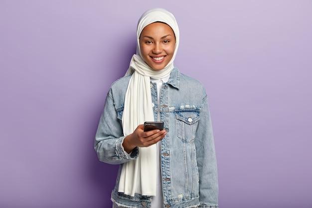 그녀의 전화와 함께 포즈를 취하는 행복 한 젊은 무슬림 여자의 초상화