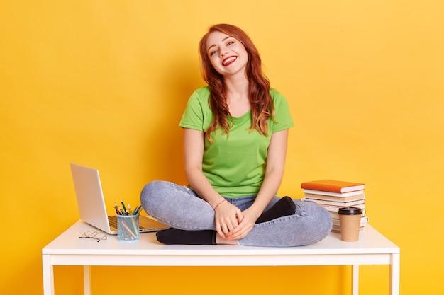 Портрет счастливой молодой читающей волосатой женщины, сидящей на столе с ноутбуком