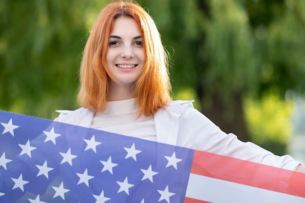 Портрет счастливой молодой рыжеволосой женщины, держащей национальный флаг сша