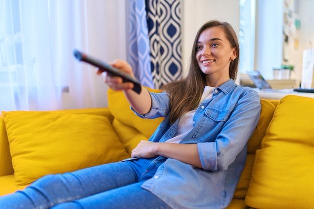 Портрет счастливой молодой довольной улыбающейся привлекательной девушки, сидящей на диване, переключающей каналы на пульте дистанционного управления и смотрящей телевизор дома в одиночестве
