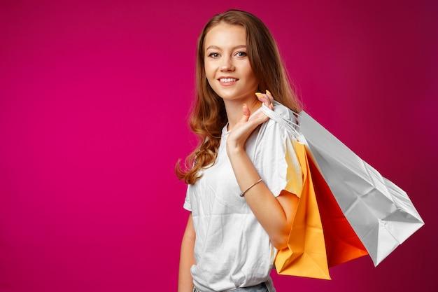 買い物袋と幸せな若い笑顔の女性のポートレート