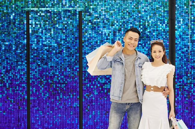 きらめく青い壁に立っている買い物袋と幸せな若いベトナムのカップルの肖像画
