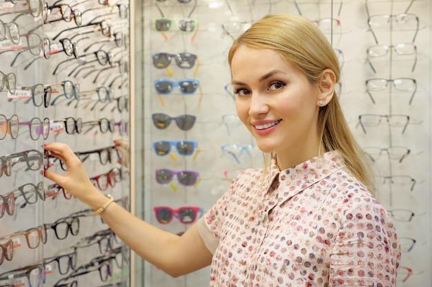 眼鏡店で新しい眼鏡を買う幸せな若い女性の肖像画。