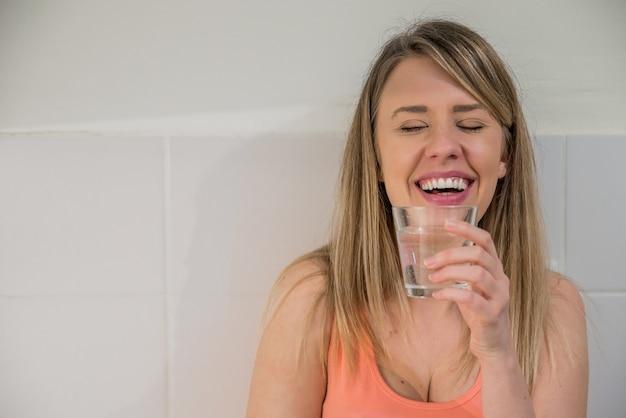 Портрет счастливый молодой женщины питьевой воды на фоне кухни. здоровый образ жизни. здравоохранение. напитки. концепция здоровья, красоты, диеты. здоровое питание.