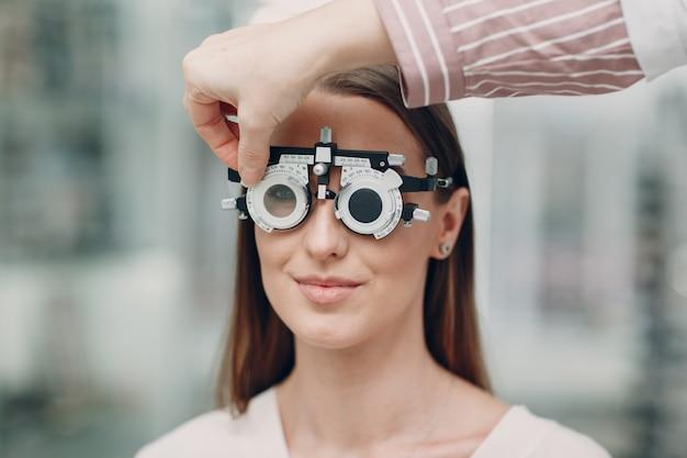 Портрет счастливой молодой женщины во время осмотра глаз у оптика оптометриста
