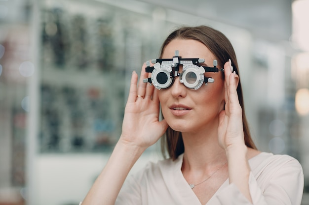 Портрет счастливой молодой женщины во время осмотра глаз у оптометриста-оптика.