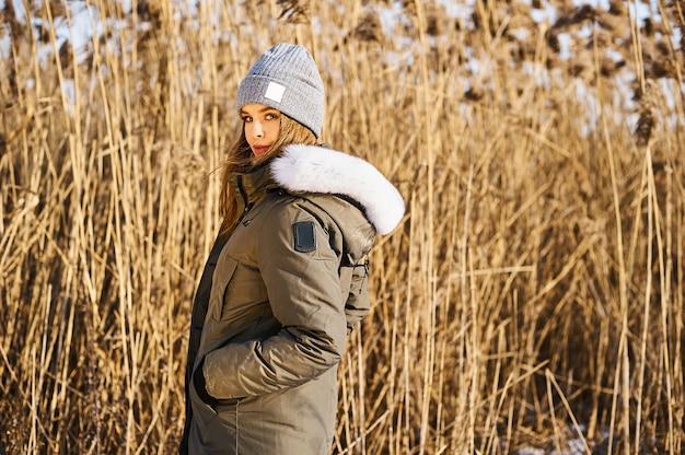 Портрет счастливой молодой женщины весело провести время в прекрасный солнечный зимний день на фоне тростника