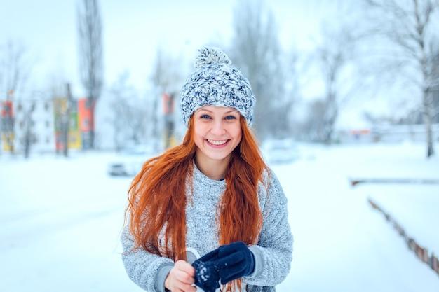 행복한 젊은 여성의 초상화는 아름다운 겨울날 즐거운 시간을 보낸다