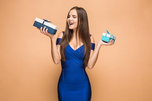 Портрет счастливой молодой женщины, держащей подарки, изолированные на коричневом фоне студии со счастливыми эмоциями