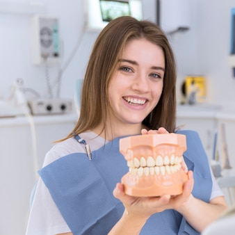 Portrait of happy young woman holding denture in her hands