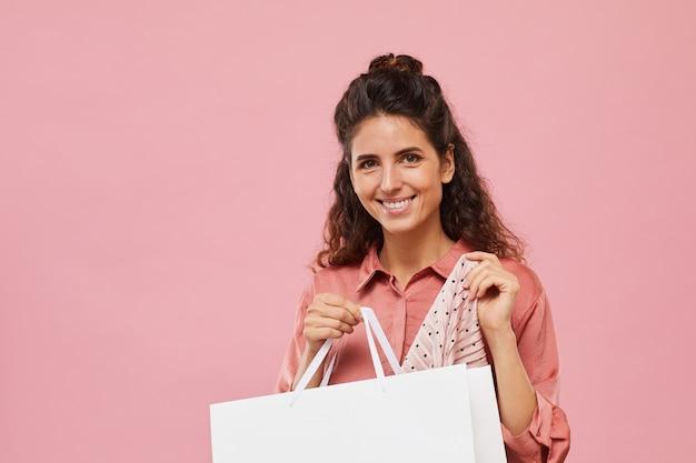彼女は新しいドレスを買う買い物袋を保持している幸せな若い女性の肖像画