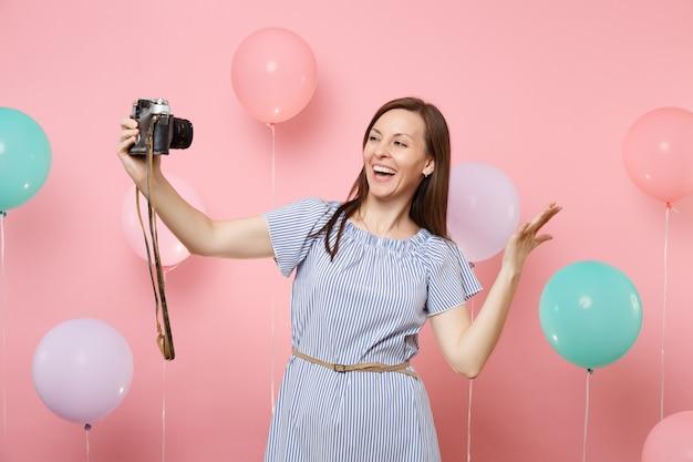 カラフルな気球でピンクの背景に手を広げてレトロなビンテージ写真カメラで自分撮りをしている青いドレスの幸せな若い女性の肖像画。誕生日ホリデーパーティーの人々は心からの感情。