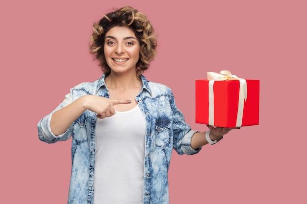 빨간 선물 상자를 들고 손가락을 가리키는 곱슬머리 헤어스타일을 한 파란 셔츠를 입은 행복한 젊은 여성의 초상화가 카메라를 바라보고 있습니다. 실내, 절연, 스튜디오 촬영, 복사 공간, 분홍색 배경