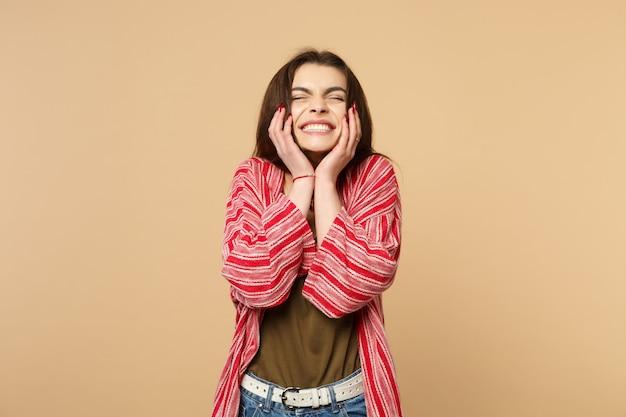 パステルベージュの壁の背景に分離された頬に手を置いて、目を閉じてカジュアルな服を着て幸せな若い女性の肖像画。人々の誠実な感情、ライフスタイルのコンセプト。コピースペースをモックアップします。