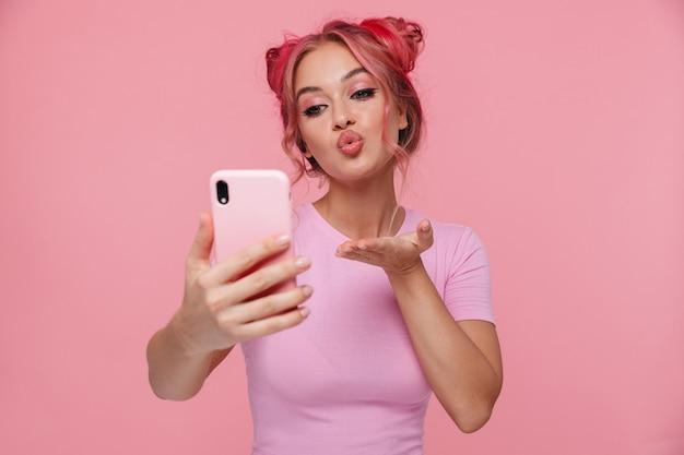 携帯電話で空気のキスを吹く色の髪とtシャツで幸せな若い女性の肖像画