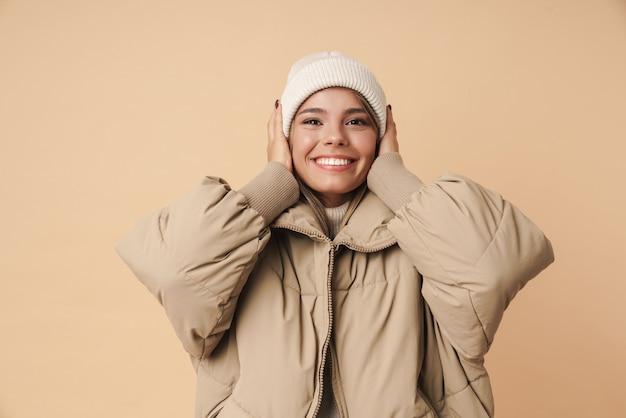 Портрет счастливой молодой женщины в зимнем пальто, схватившись за голову и улыбаясь