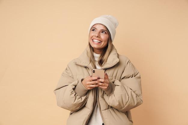 Портрет счастливой молодой женщины в зимнем пальто, смеясь и используя мобильный телефон