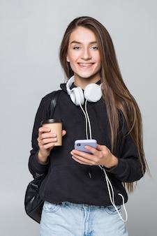Портрет счастливой молодой женщины, слушать музыку с мобильного телефона и наушники, изолированных на белой стене