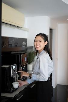 Портрет счастливого офисного работника молодой женщины, делающего кофе из кофеварки в офисе.