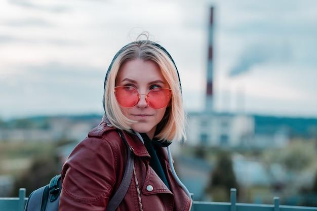 赤い眼鏡の上の幸せな若い女性の肖像画