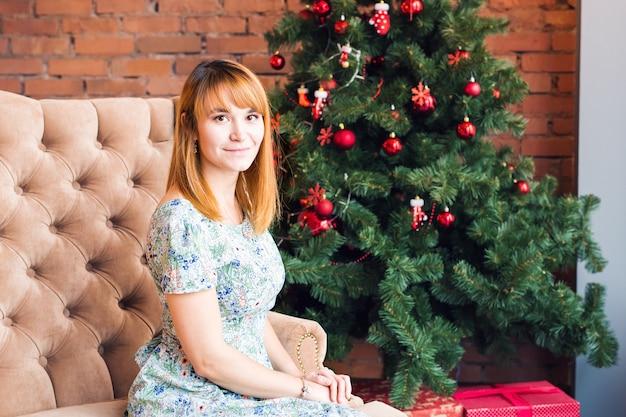 크리스마스 트리 근처 편안한 행복 한 젊은 여자의 초상화