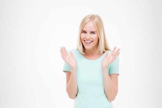 행복한 젊은 여성의 초상화는 미소를 짓고 흰 벽에 격리된 정면을 바라보고 있습니다.