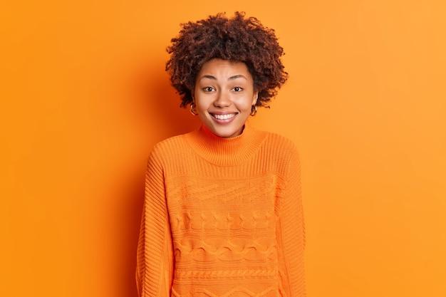 幸せな若い女性の笑顔の肖像画は広く白い完璧な歯が喜びを表現していますオレンジ色の壁に隔離されたカジュアルなセーターを着ています